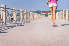 Young slim woman exercising. Sport concept. Healthy lifestyle. Young slim woman exercising on the sea pier. Female feet in sneakers outdoor Royalty Free Stock Images