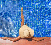 Young slim woman in hat sitting swimming pool Royalty Free Stock Photography