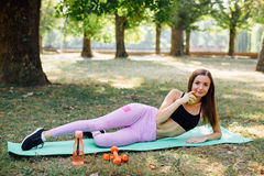 Young slim woman having snack after working out outdoors in the park. Sitting on the grass, eating juicy apple on fresh air Stock Photo