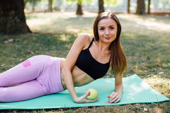 Young slim woman having snack after working out outdoors in the park. Sitting on the grass, eating juicy apple on fresh air Royalty Free Stock Image