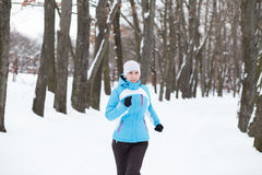 Young slim woman jogging in winter park Royalty Free Stock Images