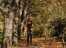 A young slim woman jumps in the park between the trees and looks joyful. Royalty Free Stock Image