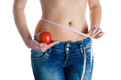 Young slim woman with measurement type and holding red apple in jeanse. Woman measuring her stomach with measuring tape Young slim woman with measurement type Royalty Free Stock Photo