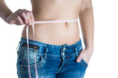 Young slim woman with measurement type. Woman measuring her stomach with measuring tape Royalty Free Stock Photography
