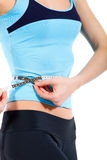 Young slim woman measuring her stomach Royalty Free Stock Photo