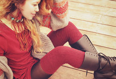 Young slim woman model dressed in warm knitted stockings and knee-high boots, hand made necklace, Stock Photo