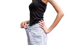 Young slim woman in oversize pair of blue jeans over white. Background Royalty Free Stock Images