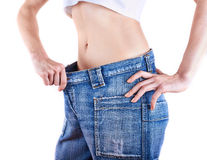 A young slim woman in oversized pair of blue jeans royalty free stock image