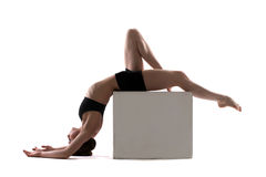 Young slim woman posing on cube in studio Stock Image