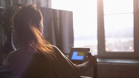 Young slim woman practicing on the bike simulator at home by window looking on the city during sunset with lens flare. Woman practicing on the bike simulator by royalty free stock photography