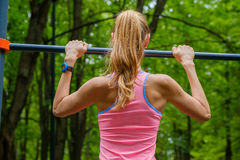 Young slim woman pulls on horizontal bar. In a park Royalty Free Stock Photos