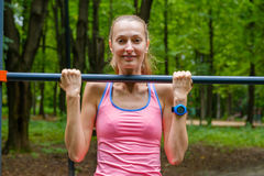 Young slim woman pulls on horizontal bar. In a park Stock Images