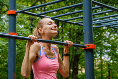 Young slim woman pulls on horizontal bar. In a park Royalty Free Stock Image
