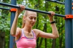 Young slim woman pulls on horizontal bar Stock Photo