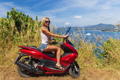 Young slim woman riding motorbike on a sea coast Royalty Free Stock Photo
