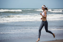 Young slim woman running on the beach. Stock Photos
