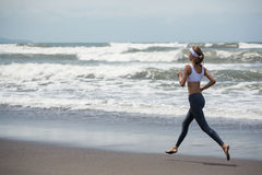 Young slim woman running on the beach. Royalty Free Stock Photos