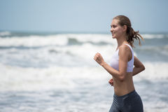 Young slim woman running on the beach. Royalty Free Stock Photography