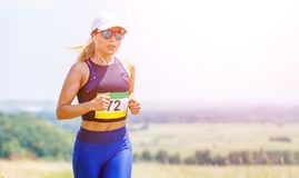 Young slim woman running trail race contest Royalty Free Stock Photography
