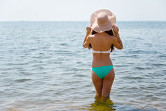 Young slim woman in sea in hat Royalty Free Stock Photo