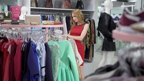 Young slim woman is shopping in clothing store, taking dress from hanger and watching, standing in trading area. Choosing new gowns stock video