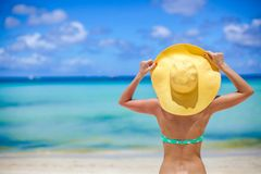 Young slim woman sitting on beach holding yellow Royalty Free Stock Images