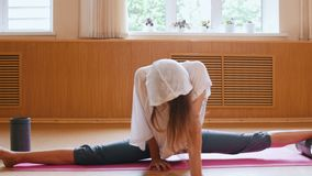 Young slim woman sitting on the yoga mat in split - using auxiliary stand under one foot - leaning forward. Mid shot stock footage