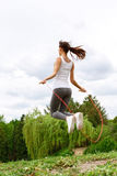Young slim woman skipping in park Royalty Free Stock Images