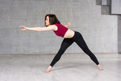 Young slim woman in sport action. Pretty young woman in red top and black leggings practicing dance element on studio background royalty free stock photos