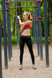 Young slim woman sports portrait on the training ground. Young slim woman stretching hand on the training ground in a park Stock Photo