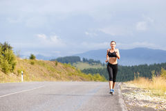 Young slim woman in sportswear jogging on the road Royalty Free Stock Photos