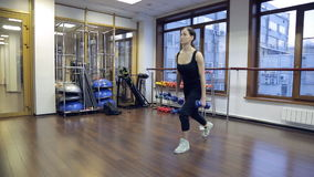 Young slim woman squat with dumbbells as weight in fitness center. stock video