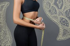 Young slim woman standing alone and measuring her waist line Royalty Free Stock Photo