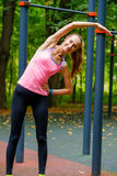 Young slim woman stretching in a training ground. In a park Stock Images