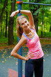 Young slim woman stretching in a training ground. In a park Stock Photography