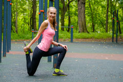 Young slim woman stretching in a training ground. In a park Royalty Free Stock Images