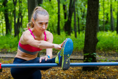 Young slim woman stretching in a training ground Royalty Free Stock Photo