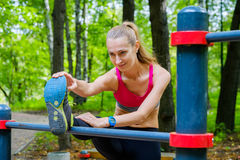 Young slim woman stretching in a training ground Royalty Free Stock Image