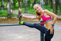 Young slim woman stretching in a training ground Royalty Free Stock Photos