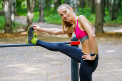 Young slim woman stretching in a training ground Stock Photos