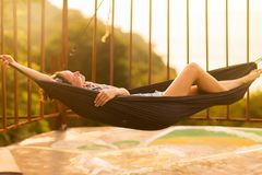 Young slim woman in tropical exotic hammock sunset lights. Young slim woman tropical exotic hammock in sunset lights royalty free stock photo