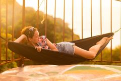 Young slim woman in tropical exotic hammock sunset lights. Young slim woman tropical exotic hammock in sunset lights royalty free stock photos