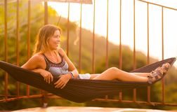 Young slim woman in tropical exotic hammock sunset lights. Young slim woman tropical exotic hammock in sunset lights stock photo
