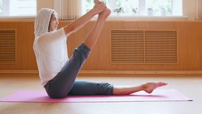 Young slim woman warming up sitting on the yoga mat and doing leg exercises - dance studio stock video footage