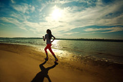 Young slim woman on water at river coast. Fitness and heath care concept, outdoors. Sunset with dramatic sky stock photography