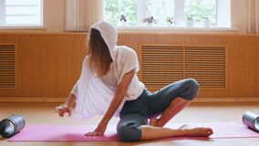 Young slim woman in white shirt using auxiliary stand under the foot to stretching in the split. Mid shot stock video