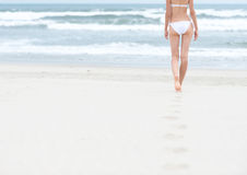Slim girl in white swimsuit walking to ocean. Royalty Free Stock Photos