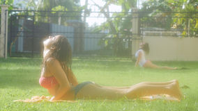 Young slim women doing yoga on the grass in the shine morning Royalty Free Stock Photos