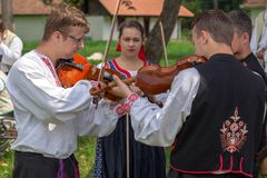 Young Slovak violin singer, in traditional costumes. TIMISOARA, ROMANIA - JUNE 8, 2018: Young Slovak violin singer, in traditional costumes, perform at the folk stock images