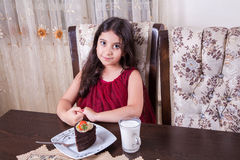 Young small beautiful middle eastern child girl with chocolate cake with pineapple, strawberry, and milk with red dress and dark e Royalty Free Stock Images